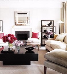 Elle Decor    Love the silver mirror and glossy black square lacquer coffee table in this chic living space. Love the gray linen slipper chair and white paint wall color! Tan red brown beige pink living room space colors.