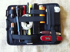 Grid-it for my EDC bag.  This Cocoon Grid-It goes into my Mountainsmith small messenger bag, to keep all of the small things organized. In this version, they are from left to right: 2-AA batteries non LCD Brinkman red sharpie black gel pen neon highliter MAC charging cord MAC USB outlet reading glasses bic lighter MAC ear phones 3x enclosed magnify glass short Cross pen large vintage car victorinox SAK