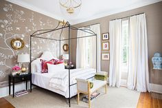 Illuminated by a clear beaded chandelier, this  stylish bedroom boasts a a black canopy bed accented with gold and dressed in gray board hotel bedding topped with white shams and red suzani pillows.