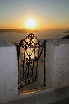 Greek island of Santorini. Sunset view of the caldera through an old rusty entrance gate. Greece Stock Photo