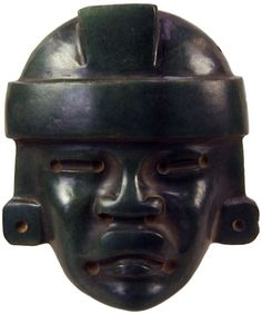 Teotihuacan green Jade mask with parted lips, frowned mouth, slit eyes, and headdress, circa 450 – 650 AD.