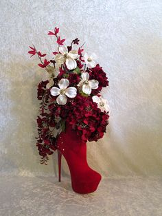 Beauty in a Shoe!! This very Unique floral arrangement is made in a real Red Suede High Heel Shoe. It showcases a beautiful combination of Reds and Creams. The flowers include Dahlia, Hydrangea, Flowering Brach, Wisteria and Beautiful Cream Dogwood with Gold Glitter and Pearls. The completed arrangement measures approx. 17 inches tall by 10 inches wide by 8 inches deep. This original arrangement has been designed and created exclusively by Always In Bloom Floral. Thanks for visiting my…
