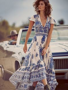 Bluebird Dress   Sweeping, semi sheer maxi dress featuring a V-neckline and cap sleeves with subtle crochet detailing. Button accents with a front slit for an added dose of drama. Smocked waist with drawstring tie makes for an effortless fit. Tiered high-low hem. Pair with one of our Signature Seamless styles to complete the look.