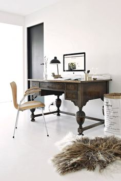 Elegant home office with an large old wooden desk, a modern leather chair, a paper bag and a fur.