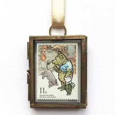 This is a beautiful miniature frame for lovers of A. A. Milnes Winnie the Pooh. It makes a lovely wall hanging for a little ones nursery or bedroom and would also make the perfect keepsake Christening / Baptism gift. This vintage style mini frame is approx. 5cm x 4cm and comes with a golden ribbon. The frame will hold one mint, 11 pence Royal Mail Winnie the Pooh postage stamp from 1979, which sees the bear alongside Christopher Robin, Eeyore and Piglet. The frame will be wrapped in bub...