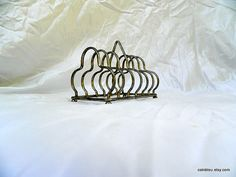 Metal toast rack. Cute with a lovely form.    Very tarnished metal.    It measures 6 long x 4.2 wide and 4.5 high.  Would be great for vintage postcards!