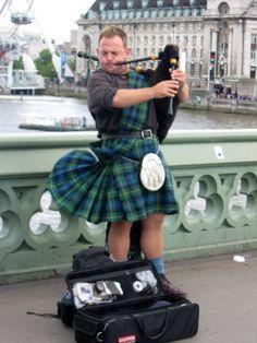 Bagpiper in Scottish attire on the Westminster Bridge, London