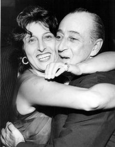 Anna Magnani gives Totò a bear hug at an awards ceremony in Rome. September, 1955