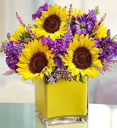Modern Enchantment™- Hand-designed arrangement of #sunflowers, #lavender stock and pink calcynia, accented with variegated pittosporum in a chic clear glass tube filled with yellow foam ribbon $54.99