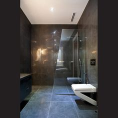Designed as a wet room, the bathroom features an angled glass blade to contain water splashes from the shower. The white and black wall-hung toilet pan echoes the angled shape of the glass, tub and basin.