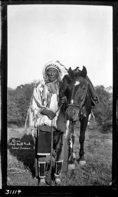 Chief Bell Rock (Biitawuash). Bell Rock holding his horse, he is wearing his war bonnet (baashbaleikkupe), war shirt (baleiittashtee) decorated with beads and ermine, a breech cloth, beaded trousers, and moccasins. He is holding a feathered coup stick. William Wildschut photograph collection. NMAI. Native American Horses, Native American Photos, Crow Indians, Cowboys And Indians, Crow Photos, Walk In The Spirit, Eskimo, War Bonnet, Historical Pictures