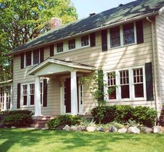 The before photo shows a classic vaulted portico with no outdoor living space. But an addition of an open porch is the perfect point of entry for ushering guests in with style. The classic columns and porch railings are painted the same white as the house trim./