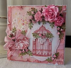 So much I like about this card! the lace on the birdcage, the white embossing with pearls on the left, the ribbon and flowers, and the distressed pink background. Pretty and vintage!
