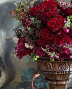 Samarcanda red garden roses and maroon dahlias in an antiqued urn // Carolyne Roehm