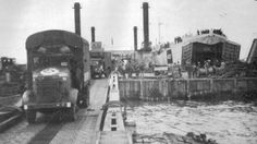 HMS LST-427 unloading trucks at a Mulberry Harbor at Normandy in June 1944.