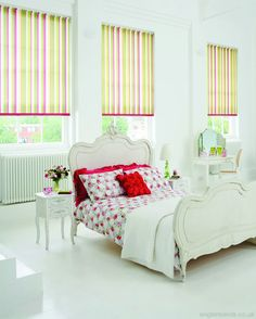 Vibrant white green yellow and pink striped roller blinds in a white bedroom