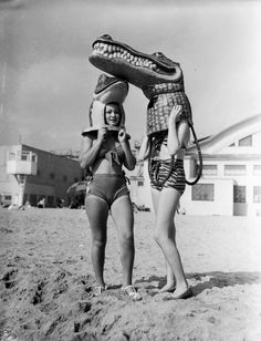 Mardi Gras celebration of 1935 at Venice Beach. Two young ladies on the beach wearing alligator masks which will be used later in the parade (via Los Angeles Public Library). °