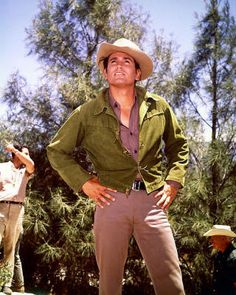 Michael Landon US actor wearing a cowboy hat and a green jacket on the set of the US television series 'Bonanza' with the figures of two men in the. Michael Landon, Bonanza Tv Show, Green News, Johnny Carson, Tv Westerns, Old Tv Shows, Classic Tv, Green Jacket, Actors & Actresses