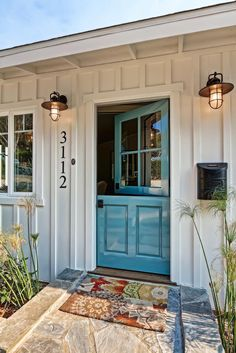 A robin's egg blue Dutch door flanked by lantern sconces creates an inviting entry. The Dutch door is a great way to open the home up to the beachy environment and is perfect for kids.