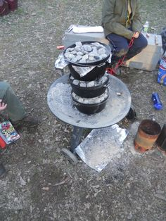 Dutch oven cooking triple stack style. Looks a little dangerous to me!