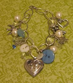Upcycled bracelet made up with vintage buttons, chandelier crystals, a heart locket, vintage skeleton key, pearls and more! SOLD