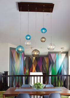 In a large space with a high ceiling, multiple pendants on a long chain draw the eye downwards, making that space seem less imposing – and when positioned carefully, can also bring symmetry to the space. Available in amber, aqua, brown, clear, or smoke, the Isla pendants by @LBLlighting feature an irregular round shape, and a hand blown organic seeded technique that leaves hundreds of bubbles suspended within the glass.