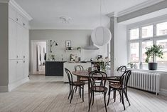 I think this spacious Swedish apartment looks amazing and I like the subtile color choices of the space and interior decoration. The large combined kitchen and living room has been painted in a greige Dark Grey Walls, Grey And Beige, Gravity Home, Vintage Stool, Interior Decorating, Interior Design, Round Dining Table, Dining Area, Black Kitchens