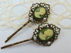 Zwei nostalgische Haarspangen aus bronzefarbenem Metall mit filigranen Fassungen und Gemmen in grün-creme. Die Fassungen sind mit Halbperlen verziert.