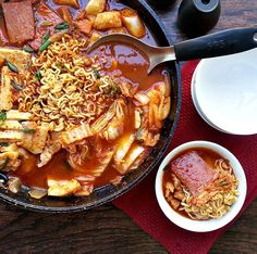 budae jjigae.  Korean army base stew. It's a hodgepodge of ingredients thrown in together from spam to ramen noodles to kimchi to various vegetables and it's oh so delicious!