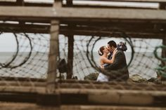 Bride and groom photographed through a lobster trap in Pictou Nova Scotia