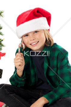 portrait of a boy holding christmas candy. - Portrait of a boy holding christmas candy against white background, Model: Josh Chapman