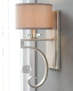 """Wall sconce with large crystal ball drop. Made of metal with a shimmery silver finish. Uses one 60-watt bulb. 7.25""""W x 8.5""""D x 17""""T. Imported."""