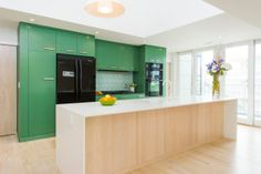 super bright interior with white walls and light wood floors that's contrasted with bold green and yellows