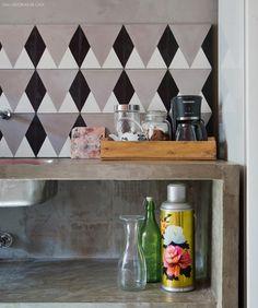 Cozinha conta com painel de ladrilho hidráulico e bancada de concreto.