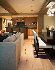 A luxury creekside residence in Vail Village, Rocky Mountains, Colorado with an open floor plan living room, kitchen, and dining area. Floor is engineered wide-plank Bavarian Oak, wire-brushed and with a custom finish. The wall paneling in the living room is reclaimed European sunburnt wood. All wood is non-toxic, sustainable, engineered wood by Arrigoni Woods.