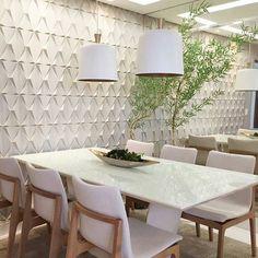 53 ambientes com revestimentos 3D para te inspirar.  Revestimento 3D branco alinhado a uma parede de espelho confere sensação de amplitude a sala de jantar.