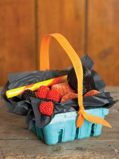 With a layer of black tissue paper and an orange ribbon, leftover berry containers can turn into perfect take-home goodie baskets.