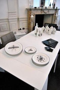 Monochrome tabletop items enhance this matt white dining table.