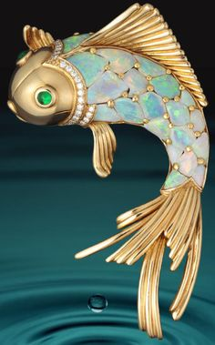 An opal, emerald and diamond brooch, Oscar Heyman & Brothers. Brooch in the form of a fish, with scales of opals, cabochon emerald eyes and further detailed by round brilliant-cut diamonds; with maker's mark for Oscar Heyman & Brothers, no. 200403; estimated total opal weight: 14.55 carats; mounted in eighteen karat gold; length: 3in. Via Bonhams.