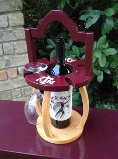 This beautiful wine caddy is crafted out of pine, hand painted and coated multiple times with polyurethane for durability. It holds one bottle of wine and four stemmed glasses. It's available in virtually any school color and emblem, or in natural stain. Wine Bottle Rack, Wine Glass Holder, Bottle Holders, Wine Rack, Alcohol Dispenser, Wine Stand, Wine Caddy, Room Design Bedroom, Wine Table