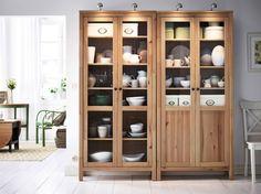 Expositor rústico con armarios HEMNES de pino macizo y puertas de cristal en un salón blanco
