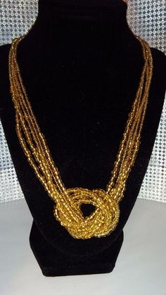 Five strand knotted gold seed bead necklace.