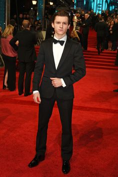 Rising Star Winner Tom Holland wearing a textured peak lapel jacket and black mohair trousers by Burberry, to the BAFTAs