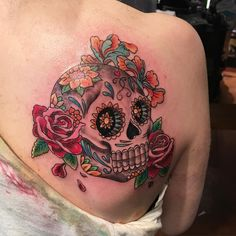Mexican skull tattoo with flowers on woman's back