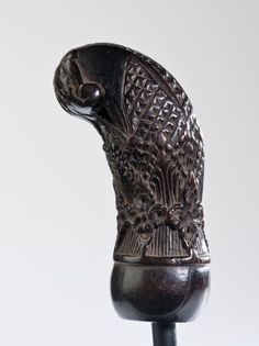 This wood keris hilt is from Madura. The detailed carving shows a classic stylized bird motif together with botanical decoration. The design style of this piece is classic and is found frequently in keris from this region.  Catalog No.: 851 Nature: Keris Hilt Origin: Madura Source: Aspidistra Collection Material: Wood Age: Unknown Price: € 480
