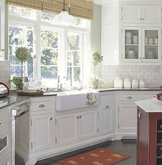 Corner farmhouse kitchen sink with large open windows above.  Beautiful-  sunlight just pours in.