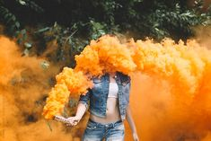 Young woman with orange smoke bomb at the nature.