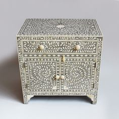 Intricate bone inlay work with slate blue ground.  One drawer and two door cabinet below with white bone flower knobs.
