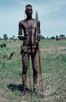 Portrait Of Dinka Warrior Carrying Spears With His Body Painted With A Mixture Of Dung And Ash And Wearing Traditional Jewellery