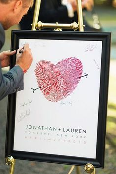 first this is so cute red fingers prints enlarged and lapped together to create a heart with the (always trusty cupids arrow). so this print is framed and used as your guest book . after the wedding you'll hang it on your wall and remember your wedding forever.